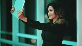 Ung flicka för blandat lopp som tar selfiebilden med minnestavlan modern teknologi arkivfilmer