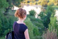 Ung flicka från kullen som ser floden Flickan är i naturen Beundra skönheten av nature_ royaltyfria bilder