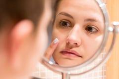 Ung flicka framme av en badrumspegel som s?tter kr?m p? en r?d finne r arkivfoton