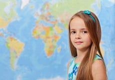 Ung flicka framme av världskartan Royaltyfria Bilder