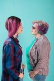 Ung flicka, hög kvinna i färgrik kläder och frisyr höfter Fotografering för Bildbyråer