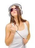 Ung flicka hör musik vid hörlurar Arkivfoton