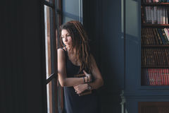 ung flicka i arkivet som står fönstret i tanke Royaltyfri Foto