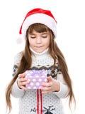 Ung flicka i ask för gåva för röd santa hatt hållande Se på gåvan Isolerat på vit Arkivbilder