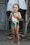 Ung flicka i baddräkten som rymmer en höna i henne armar Royaltyfria Foton