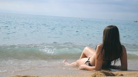 Ung flicka i bikinin som ligger på stranden och att solbada för hav Härlig oigenkännlig kvinna som kopplar av på havkust under arkivfilmer