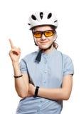 Ung flicka i cykelhjälmpunkter till utrymme, isolering på vit Royaltyfri Fotografi