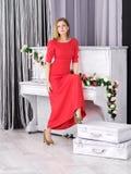 Ung flicka i den röda klänningen som står det near pianot Royaltyfri Fotografi