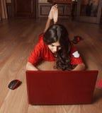 Ung flicka i den röda skjortan som ligger på golvet och arbetena över en bärbar dator Royaltyfri Foto