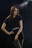 Ung flicka i den svarta T-skjortan som poserar i studion som rymmer hennes händer på midjan på svart bakgrund arkivfoton