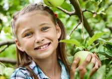 Ung flicka i en äpplefruktträdgård arkivfoto