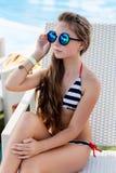 Ung flicka i en baddräkt på en hylla vid pölen Arkivfoton