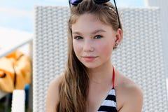 Ung flicka i en baddräkt på en hylla vid pölen Arkivbilder