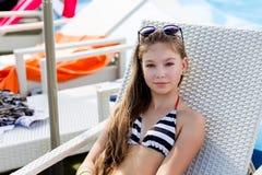 Ung flicka i en baddräkt på en hylla vid pölen Arkivfoto