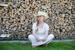 Ung flicka i en cowboyhatt på bakgrund av trä Fotografering för Bildbyråer