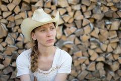 Ung flicka i en cowboyhatt på bakgrund av trä Royaltyfria Foton