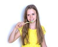 Ung flicka i en gul klänning som borstar hennes tänder Arkivbild