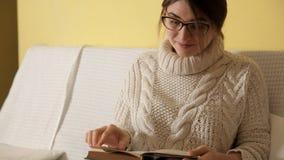Ung flicka i en hemtrevlig varm tröja på en vinterhemafton som sätter på exponeringsglas som läser en bok Vinter Hus flicka lager videofilmer