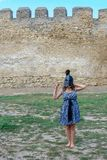Ung flicka i en klänning med en hjälm på hennes huvud nära fästningväggen royaltyfri fotografi