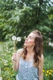 Ung flicka i en klänning som blåser maskrosen i vårträdgård royaltyfri foto