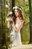 Ung flicka i en lång vit klänning, med en krans på en gunga i studion Royaltyfri Foto