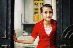 Ung flicka i en röd klänning bredvid en traditionell träport fotografering för bildbyråer