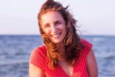 Ung flicka i en röd klänning som ler på bakgrunden av havet Arkivbild