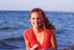 Ung flicka i en röd klänning som ler på bakgrunden av havet Arkivfoto