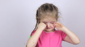 Ung flicka i en rosa skjorta som gnider henne ögon stock video