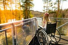 Ung flicka i en rullstol på en balkong som in ser naturen Arkivfoto