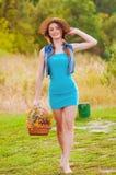 Ung flicka i en sugrörhatt med en korg av lösa blommor Fotografering för Bildbyråer