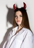 Ung flicka i en vit skjorta för man` s med röda horn som rymmer treudden och blickar som nätt jäkel Royaltyfri Fotografi