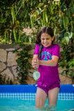 Ung flicka i ett baddräktförsök att fånga vattenballongen Arkivbild