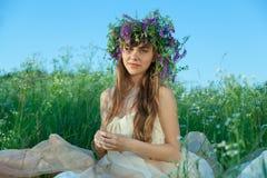 Ung flicka i ett fält av blommor Arkivbild