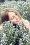 Den härliga ung flicka i ett gräs sätter in av rosmarinar Royaltyfria Bilder