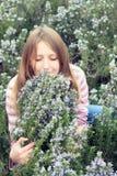Den härliga ung flicka i ett gräs sätter in av rosmarinar Arkivbild