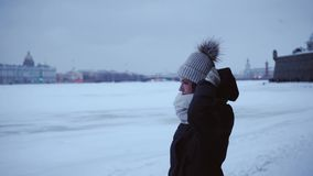 Ung flicka i ett varm omslag och hatt i förkylningen Ung kvinna på en bakgrund av snödrivor och en snöig stad Vinter arkivfilmer