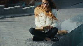 Ung flicka i exponeringsglas som läser en bok stock video