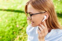 Ung flicka i exponeringsglas som utomhus lyssnar till musik till och med trådlös hörlurar royaltyfri bild