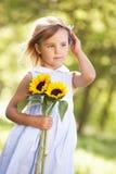 Ung flicka i fältHoldingsolros royaltyfri fotografi