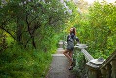 Ung flicka i färdig lugn och pacificering i en härlig och elegant klänning på naturen på våren i parkera arkivfoto