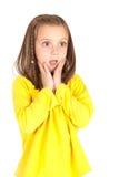 Ung flicka i gult gulligt skrämt uttryck royaltyfria foton