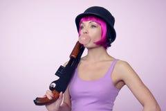 Ung flicka i hjälm med en hagelgevär och en bubbelgum Arkivfoton
