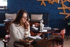 Ung flicka i kafét, bok, läsning, kaffe Arkivfoto