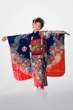 Ung flicka i kimono på vit Fotografering för Bildbyråer