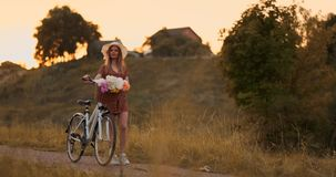 Ung flicka i klänning som går på vägen med cykeln och blommor arkivfilmer