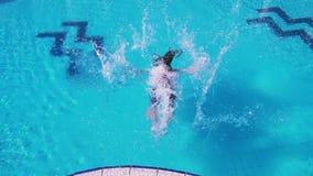 Ung flicka i klänningen som faller till simbassängen arkivfilmer