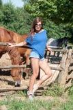 Ung flicka i lantgården som omges av hästar Arkivbilder