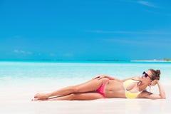 Ung flicka i ljus bikini som garvar på den tropiska stranden Royaltyfri Bild