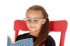 Ung flicka i moderiktiga blåa exponeringsglas som läser en bok Arkivbilder